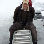 Man on ladder on frozen creek